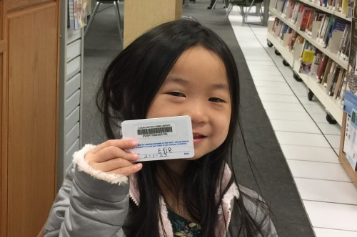 Young girl holding her first library card