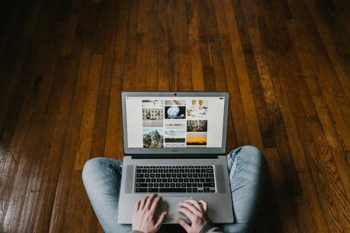 Man sitting on wood floor using laptop